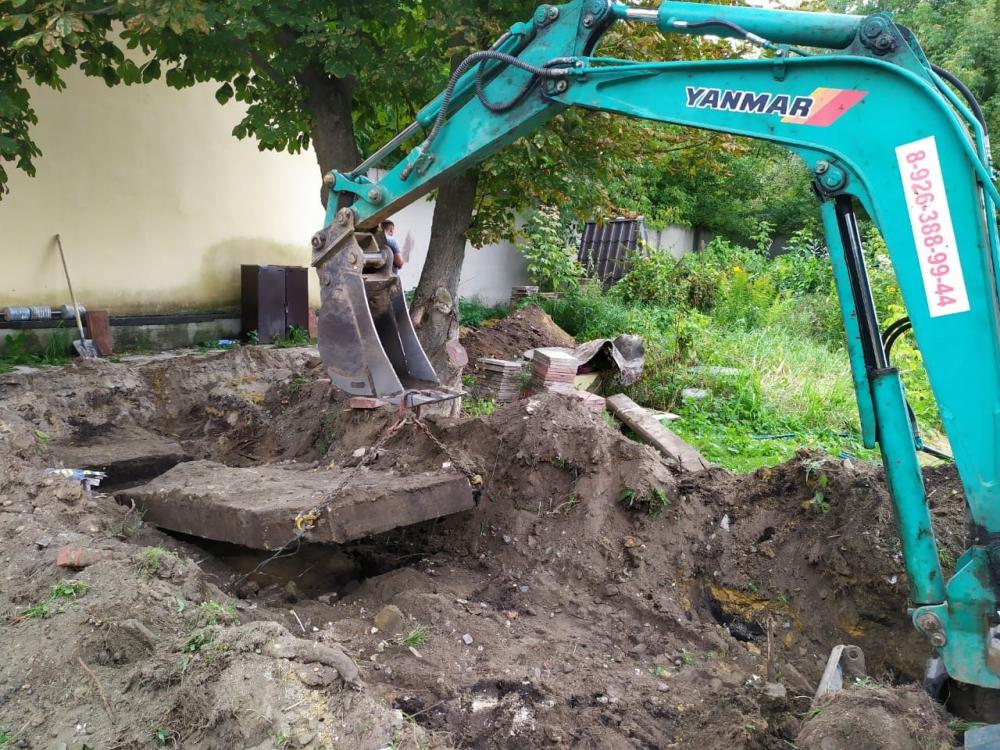Мини экскаватор работает по адресу деревня Леоново, Раменский район. Поднимаем плиты из земли при помощи ковша.
